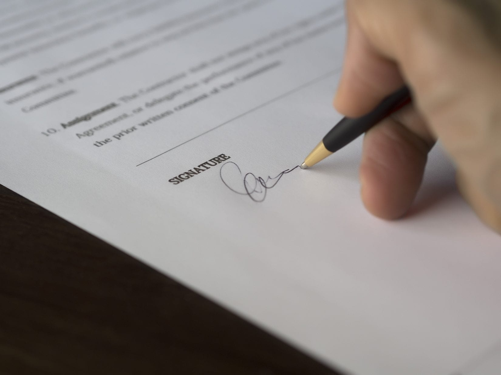 A man signing a subject-free offer for a house purchase